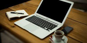 A szövegíró otthoni irodája laptoppal, jegyzettömbbel és kávéval